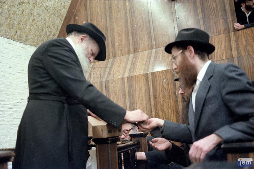 Rabbi Katzen receiving coins from the Rebbe to distribute to his students. (Photo: JEM)