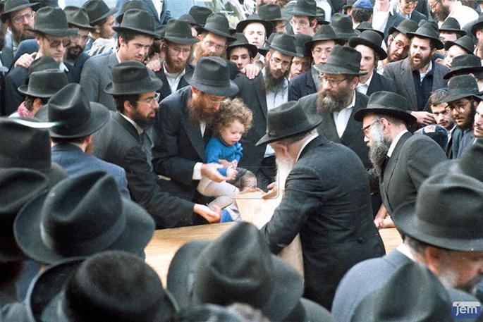 Rabbi Shmarya Katzen with one of his children receiving a coin for charity from the Rebbe. (Photo: JEM)