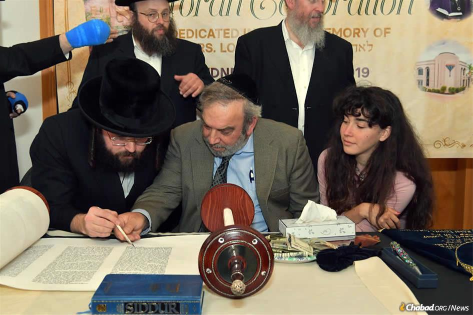 Dr. Howard Kaye inscribes a letter in a Torah scroll dedicated in memory of his wife, Lori Kaye, as their daughter Hanna looks on. Lori Kaye was murdered by an anti-Semitic gunman who entered the Chabad of Poway synagogue on the last day of Passover and began shooting during Shabbat-morning services.