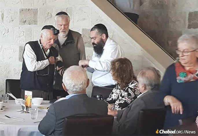 Edelkopf assists a conference participant in the mitzvah of tefillin.