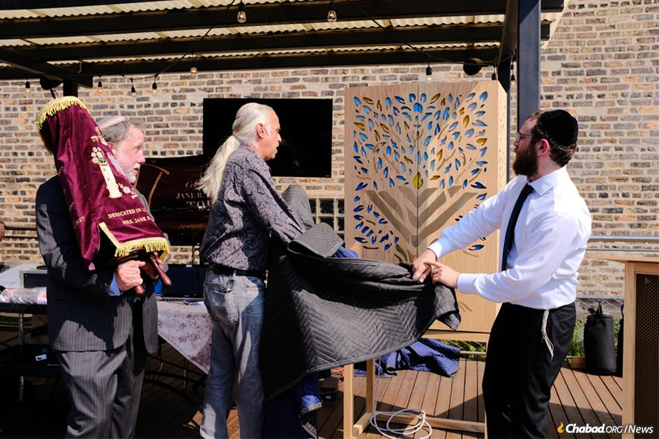 From left: David Rosenberg, James Geier and Rabbi Avraham Kagan at the dedication of a new Torah scroll and custom-designed portable ark for the River North neighborhood of Chicago.