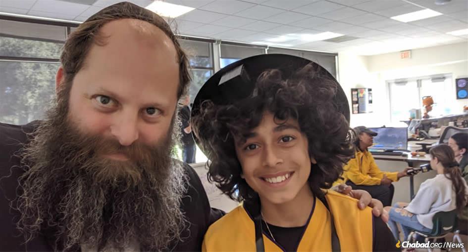 Rabbi Chaim Bryski helps a teen put on tefillin at a California wildfire evacuation center.