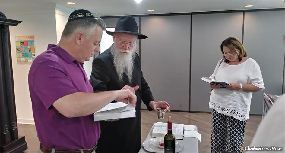 Rabbi Shmuel Notik makes the traditional blessings as Ilya, who was born in the Soviet Union, is given the Hebrew name Yosef Yitzchak Meir, following his brit milah. Yosef Yitzchak Meir's wife, Alina, looks on.