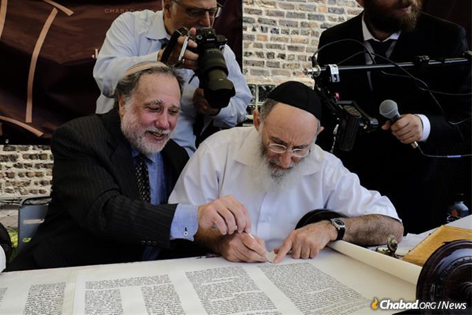 David Rosenberg inscribing a letter in the Torah scroll.