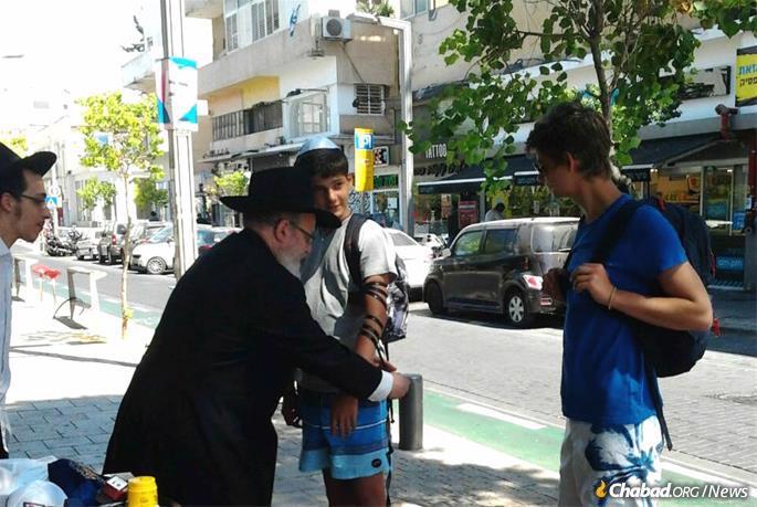 New tefillin stations have popped up around Israel since the rocket fire began on Nov. 12. Here, Rabbi Yosef Gerlitsky helps a teen put on tefillin in Tel Aviv.