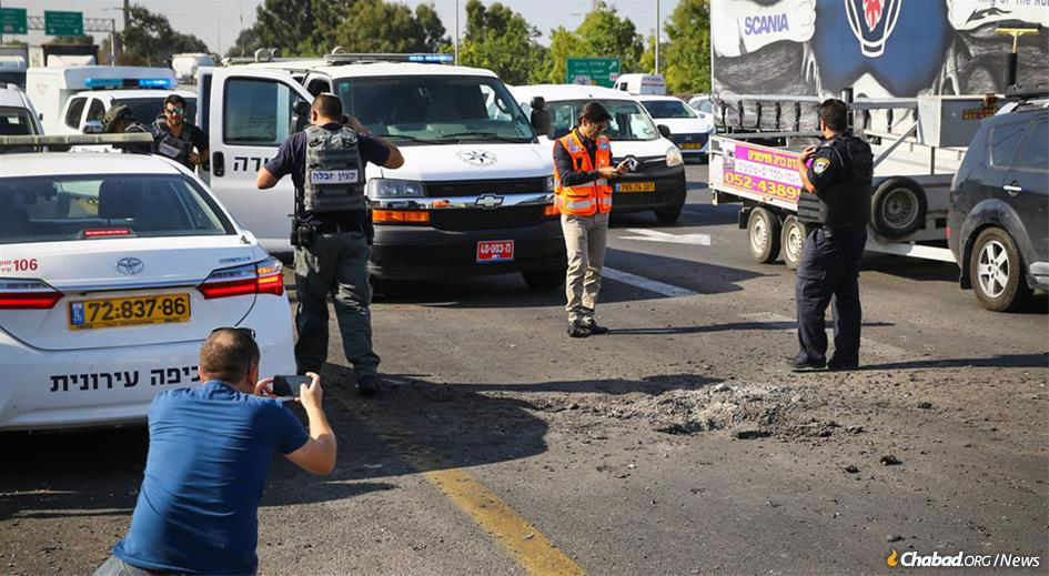 A rocket fired from Gaza hit a busy road near Gan Yavne, barely missing Tuesday-morning traffic. The barrage of more than 250 missiles continued on Wednesday, targeting Israel's center and south. (Photo: Flash90)