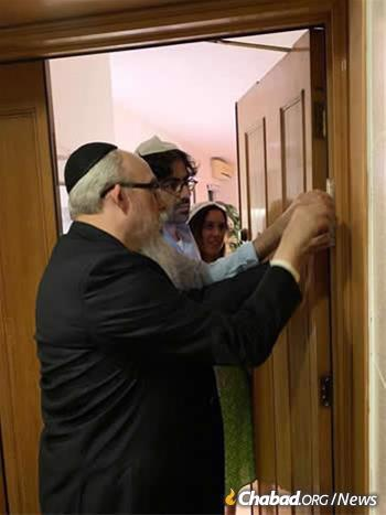 Rabbi Mordechai Avtzon, founder and co-director with his wife, Goldie, of Chabad of Hong Kong, helps residents affix a mezuzah to their door.
