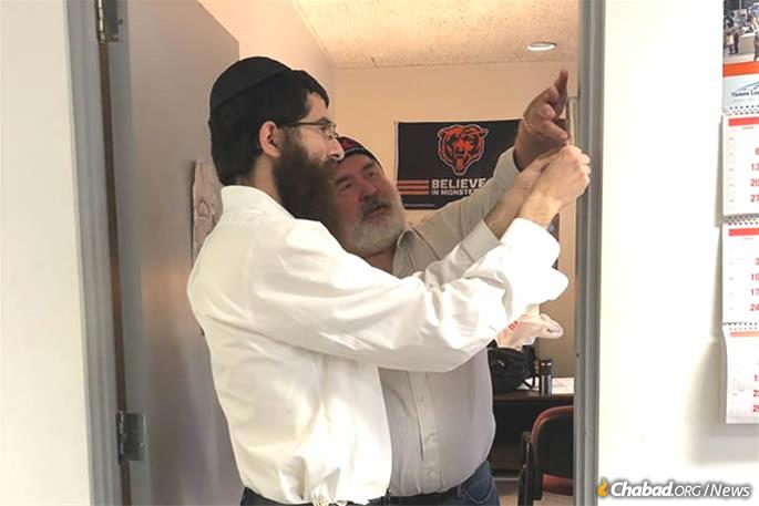Rabbi Sholom Ber Wolberg assists a Jewish business owner in Glencoe affix a mezuzah.
