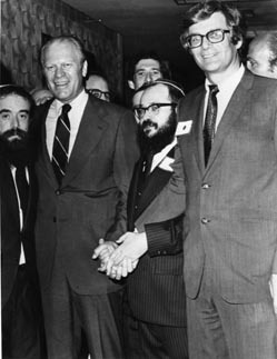 President Gerald Ford is greeted by Rabbi Abraham Shemtov (left), national director of American Friends of Lubavitch; Rabbi Moshe Feller (right), Chabad-Lubavitch emissary to Minnesota; and Senator Rudy Boschwitz; at the American Friends of Lubavitch Philadelphia dinner, May 1975.