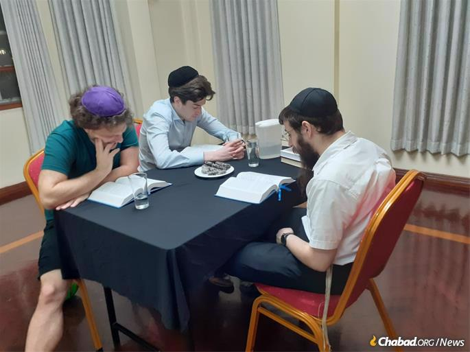 The rabbi learns Torah with young students.