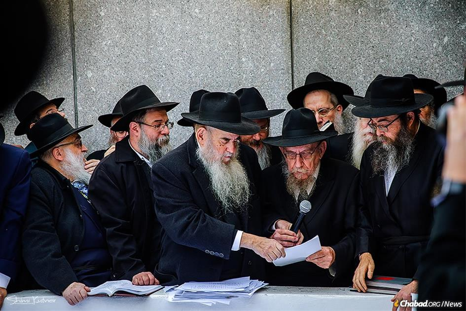 """The """"pan klali"""" letter, which was signed by many Chassidim, was read at by Rabbi Moshe Lazar, Rav of Chabad-Lubavitch in Milan, Italy, second from right, and assisted by Rabbi Moshe Kotlarsky, vice chairman of Merkos L'Inyonei Chinuch, the educational arm of the Chabad-Lubavitch movement. (Photo: Shimi Kutner/Kinus.com)"""