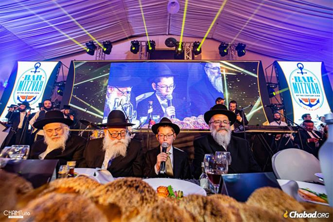 Flanked by the grandfathers who helped raise him, Moshe recites the traditional Chassidic bar mitzvah discourse.