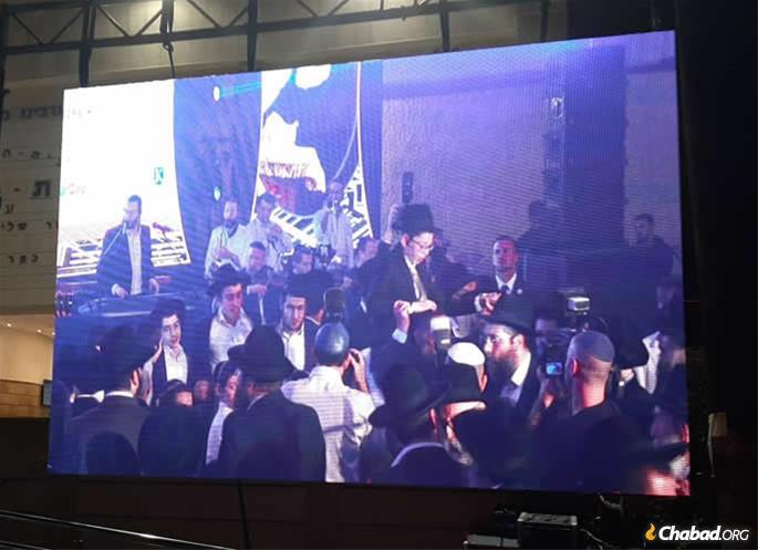 The festivities were shown on a screen outside the packed banquet hall. More festivities were planned for Monday afternoon at the Western Wall plaza, with live music, dancing and further celebration. (Photo: Dovid Sugar)