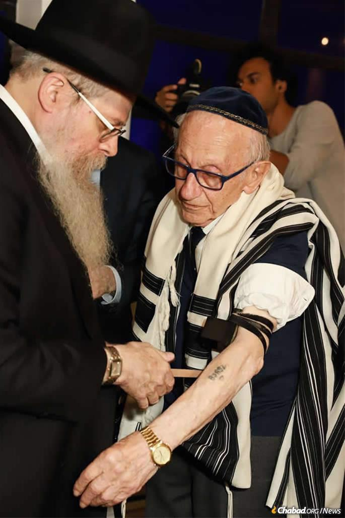 Rabbi Dovid Weitman, left, helps Andor Stern put on tefillin for the first time in his life. Stern is the only known Holocaust survivor to have been born in Brazil.