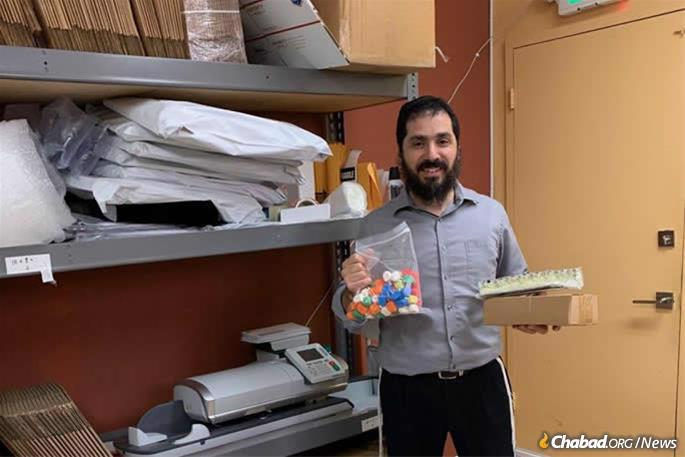 Rabbi Elie Estrin, an Air Force Reserves Chaplain and Military Personnel Liaison for the Aleph Institute helps pack Chanukah packages for worldwide distribution. He is leading the Chanukah programs at Patrick Air Force Base and the U.S. Southern Command in Florida.