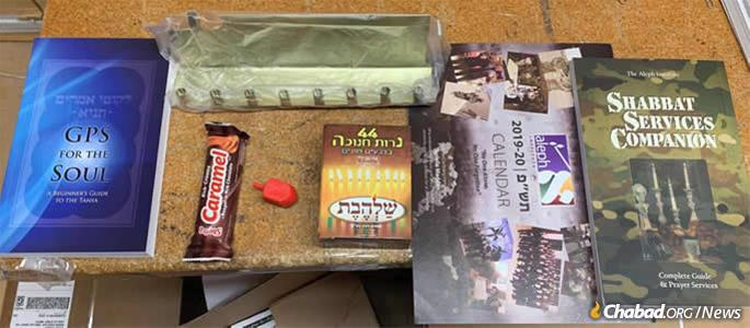 Boxes sent by Aleph Institute to U.S. military personnel around the world are filled with all things Chanukah, including menorahs, boxes of candles, dreidels, chocolate bars, Jewish calendars and books.