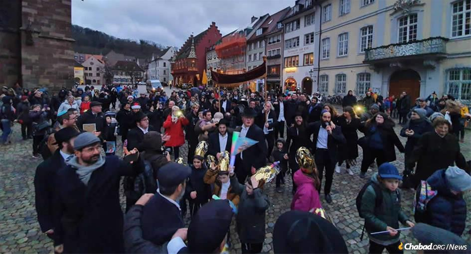 The Jews of Freiburg, Germany, march with joyful abandon on a street once named for Adolf Hitler against a backdrop of blaring Chassidic music to inaugurate a new Torah scroll and Chabad center.