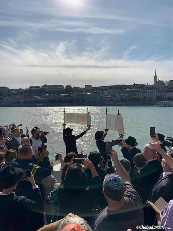 Raising the new Torah scrolls by the historic Danube River.