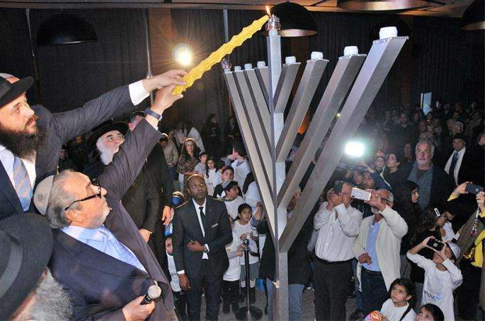 Serge Berdugo, King Mohammed VI's ambassador-at-large, kindles the giant menorah for the first night of Hanukkah 2019 as Rabbi Banon and more than 800 members of Casablanca's Jewish community look on.