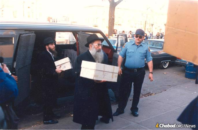 Rabbi Dovid Raskin, center, with a box of books being returned to the Library of Agudas Chasidei Chabad.