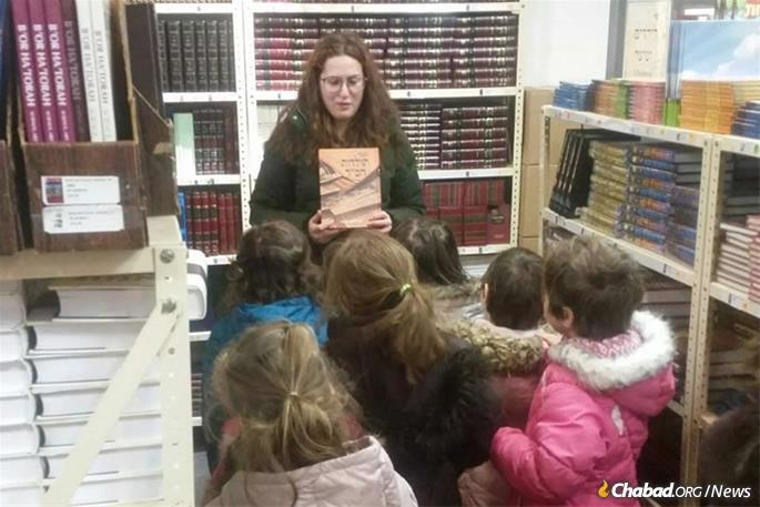 The Rebbe encouraged people of all ages to mark Hei Tevet by buying or reparing Jewish books, then studying them. A group of young girls with their teacher in Kehot's showroom. (Photo: Kehot Publication Society)