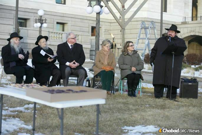Gov. Tim Walz (third from left), First Lady Gwen Walz (third from right) and Lt. Gov. Peggy Flanagan (second from right) joined Chabad-Lubavitch emissaries at the menorah-lighting in front of the State Capitol in St. Paul, Minn.