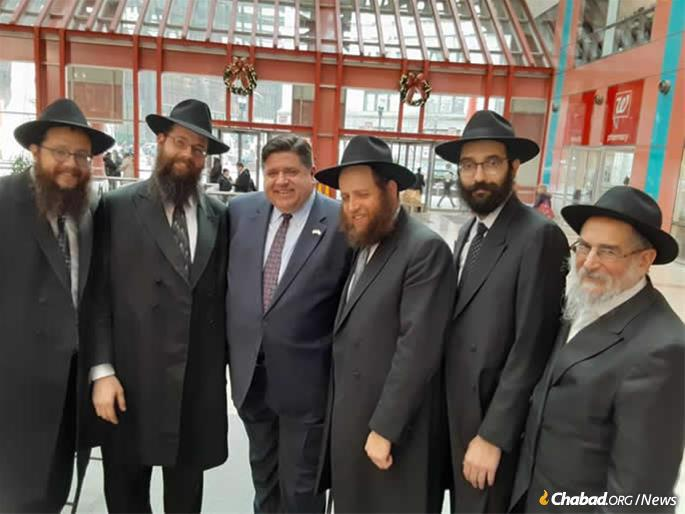 J. B. Pritzker joined Chabad-Lubavitch rabbis to unveil Illinois' official state menorah on Dec. 17 at the James R. Thompson Center, which houses the Illinois State government offices.