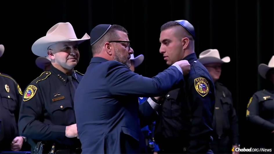 Seth Frydberg was sworn in as the newest deputy sheriff in Bexar County, Texas, with the help of his father, Felix Frydberg, center, the son of Holocaust survivors, as Sheriff Javier Salazar, left, looked on.