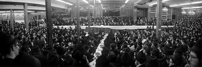 The Rebbe, Rabbi Menachem M. Schneerson of righteous memory, leads a farbrengen in the main synagogue of 770, Shevat 1976.
