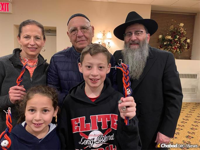 Rabbi Anschelle Perl and guests at the Havdalah ceremony at the conclusion of Shabbat in Mineola, N.Y.