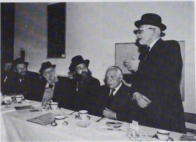 Dayan Fisher (right) speaks at a reception in honor of Rabbi Simcha Wasserman and Rabbi M. Chodosh of the Ohr Elchonon Yeshiva. Also seen (left to right) Dayan G. Lopian, Dayan I. Gukovitski, Rabbi Wasserman, Rabbi Chodosh, and Mr Morris Lederman.