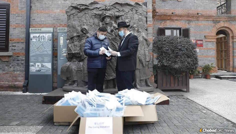 In front of a memorial plaque at Shanghai's Jewish Refugee Museum, Rabbi Shalom Greenberg and a local official discuss the 10,000 protective face masks that Chabad will be distributing to elderly Chinese.