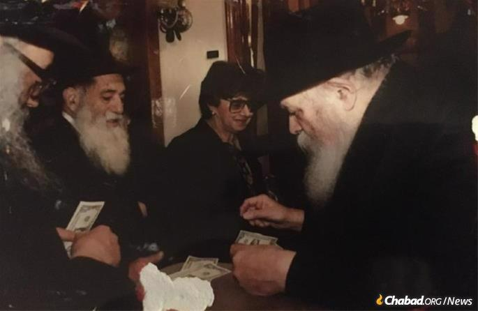 Shmuel Isaac and Miriam Popack receive a dollar and blessing from the Rebbe.