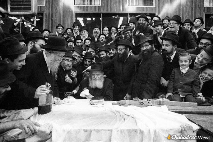 Touboul at a farbrengen with the Rebbe in the 1970s.