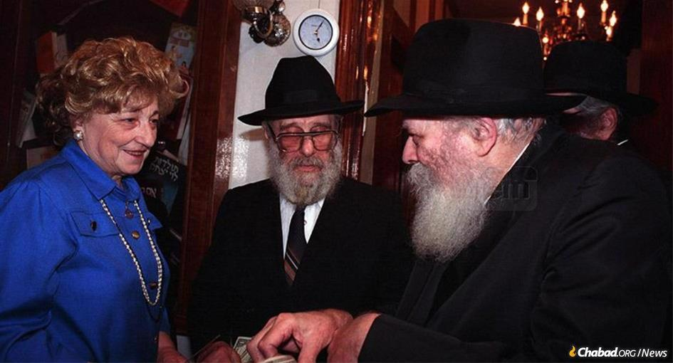 Guta Schapiro receives a dollar and a blessing from the Rebbe as her husband, Rabbi Levi Yitzchak Schapiro, looks on. (Photo: JEM)