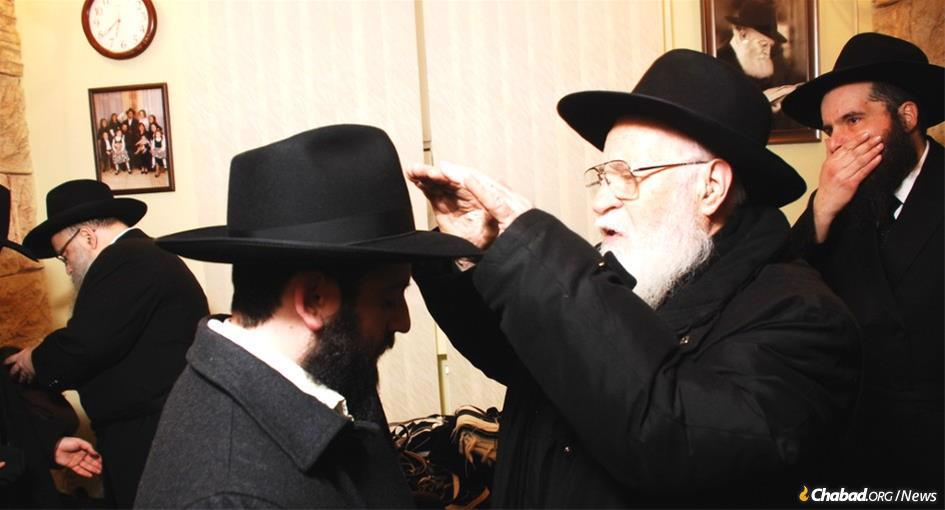Rabbi Gedalya Korf, who passed away Monday at age 90 from the coronavirus, was a quiet warrior who was among the founders and leaders of Lishkas Ezras Achim. Born in Kharkov, USSR, he is seen here blessing his grandson at his wedding in Kharkov. Korf's grandson married the daughter of the Chabad emissaries in the city from which the elder Korf had escaped.(Photo: Jewish Community of Kharkov)