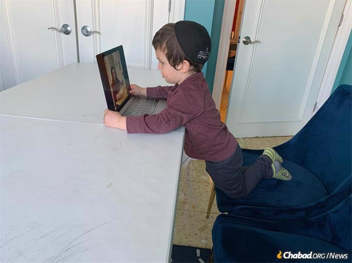 A preschool student at Oholei Torah interacts with his teacher from home via the computer. Crown Heights' Jewish schools shut their doors due to COVID-19 on Friday, March 13, they were all online by Monday, March 16.