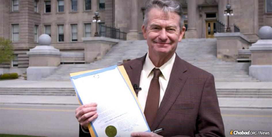 """Idaho's Gov. Brad Little reads his state's """"Education and Sharing Day"""" proclamation in front of the State Capitol building."""