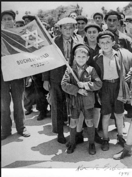 Israel MeirLau no porto de Haifa, a caminho do campo de detenção de Atlit, segurando uma bandeira com outros sobreviventes de Buchenwald. Atrás da bandeira à esquerda - seu irmão Naftali (Foto: acervo YadVashem)