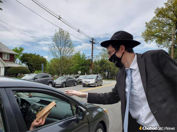 Rabbi Mendy Kaminker distributes a mask at Chabad of Hackensack's Drive-Through.