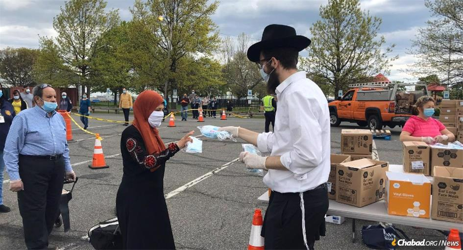 Rabbi Yisroel Bennish distributes protective masks in Bayonne. More than 150,000 masks were handed out by Chabad respresentatives and volunteers in New Jersey.