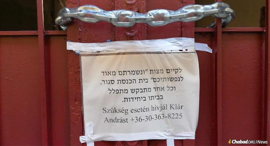 """A sign attached to the padlocked door of the Shas Chevra Lubavitch synagogue in Budapest, Hungary, reads: """"To fulfill the mitzvah of 'you shall guard your lives very well,' the synagogue is closed. Everyone is requested to pray individually at home."""" (Photo: Tamás-Haim www.tfilin.hus)"""