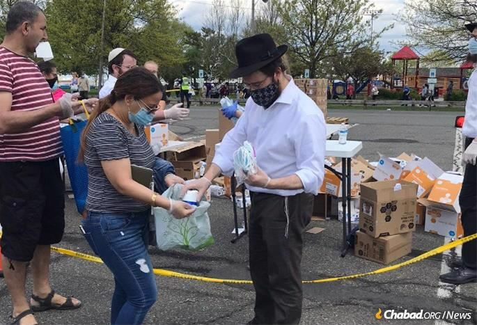 Rabbi Moshe Schapiro hands out bags with supplies and a note encouraging recipients to do a good deed.