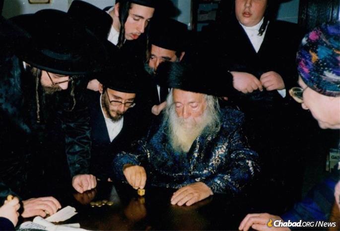 Rebbetzin Halberstam, far right, looks on as her husband spins a dreidel on Chanukah.