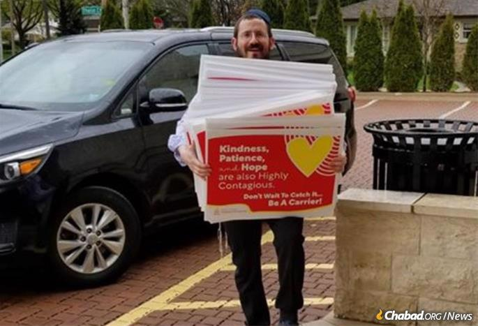 Rabbi Moshe Teldon holds hundreds of newly printed signs for distribution.