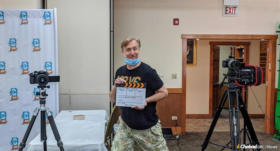 Comedian and filmmaker Brett Walkow, in the near-empty Lubavitch Chabad of Skokie social hall, prepares the presentation to show on the videotron at this year's CTeen dinner event.
