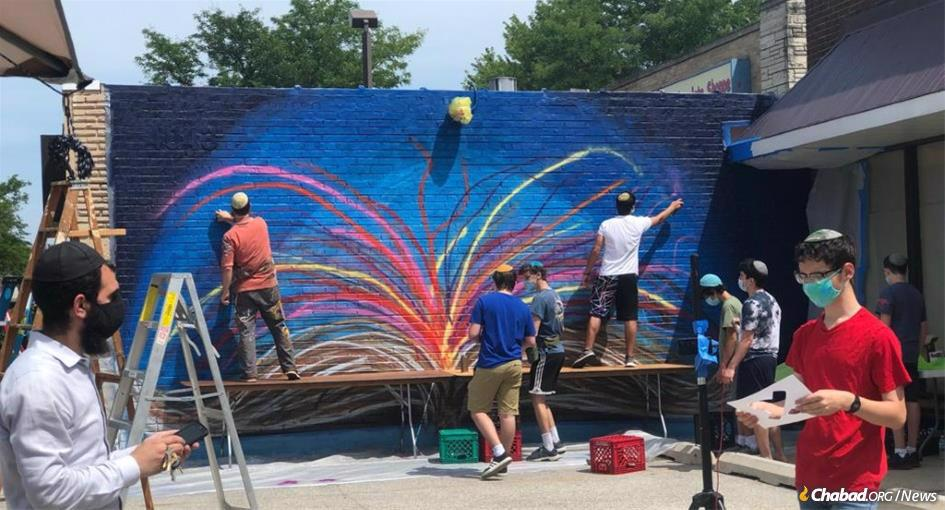 A group of teens in Skokie, Ill., teamed up with East Coast artist Yitzchok Moully, second from left, to paint a colorful, uplifting mural.