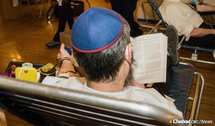 Taking time to study Torah while donating. (Photo: Shmulik Serebryanski)