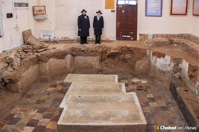 Thaler (left) and Wilhelm at the uncovered mausoleum and gravesite. Until now those coming to pray were in fact standing right over the graves of Rabbi Levi Yitzchak and his sons, something that will now be rectified. (Photo: Chabad of Berdichev)