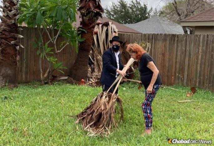 Rabbi Asher Hecht helps a woman remove debris following the hurricane.
